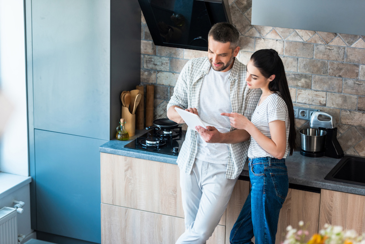 married couple using digital tablet together in kitchen, smart home concept