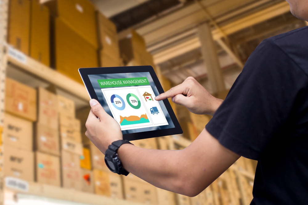 Smart warehouse management system.Worker holding a tablet on blurred warehouse as background