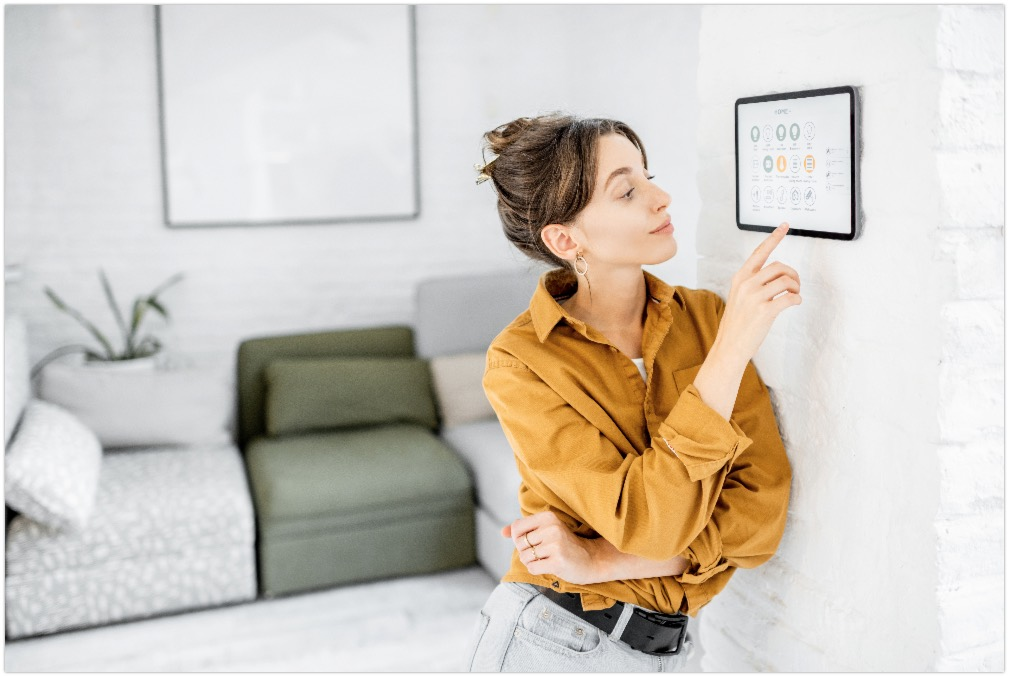 Woman controlling home with a digital touch screen